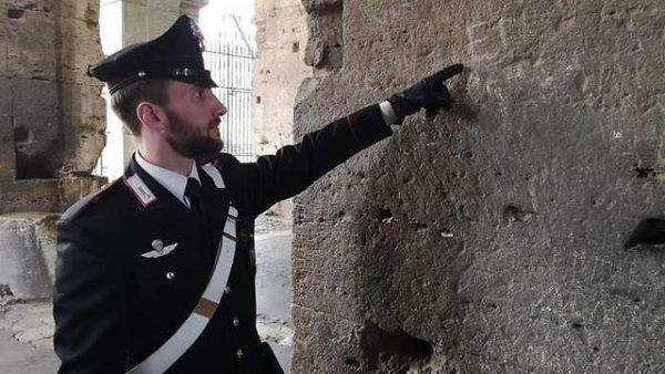 שוטר איטלקי בקולוסיאום, מצביע על החריטה. צילום: ANSA